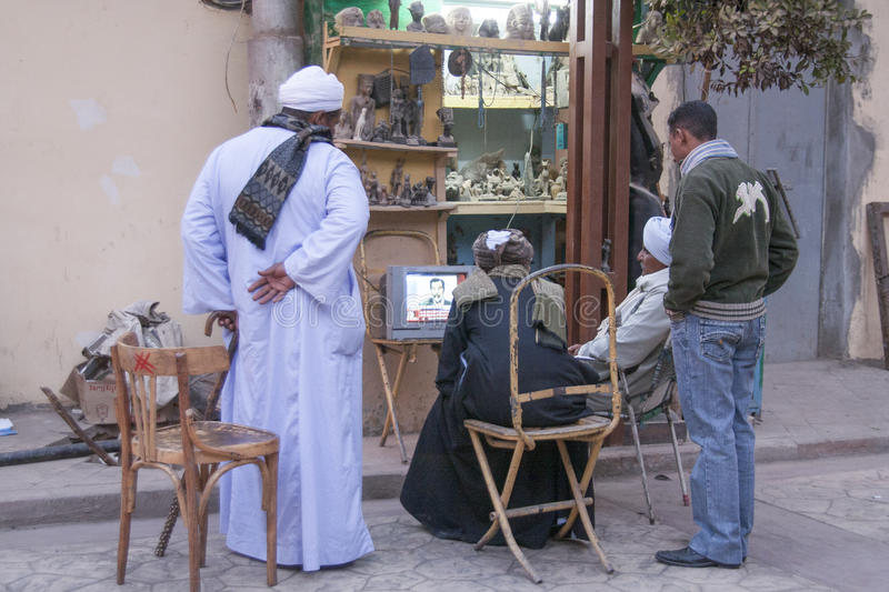 Luxor, Egypt - December 30, 2006: People on the street watching. On TV the execution of Saddam Hussein stock photos