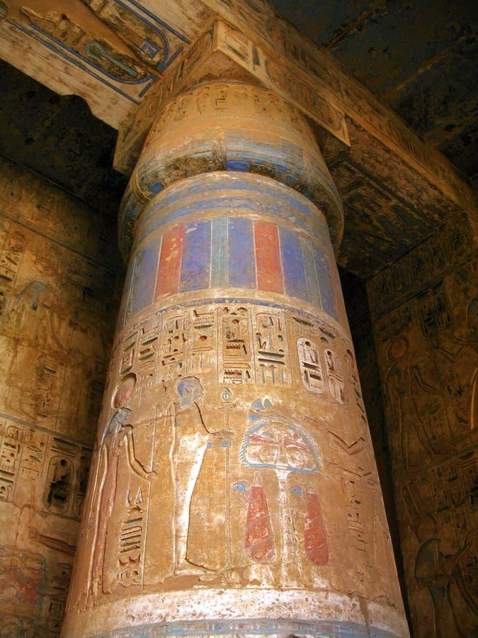 Luxor: Polychromed column at Medinet Habu temple. Luxor: Polychromed column with bass-reliefs at the temple of Medinet Habu, dedicated to Rameses III. West bank stock images