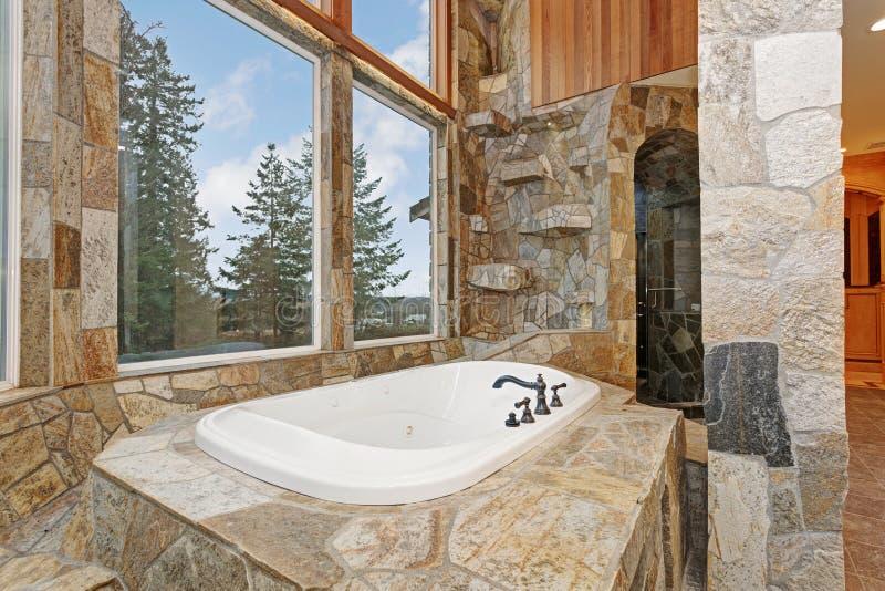 Luxueus daling-in Badkuip met panelen bekleed in steentegels stock afbeelding