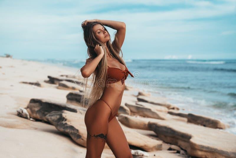 Luxueus getatoeeerd jong meisje in het rode zwempak stellen op het strand Leuke blondevrouw met het lange haar ontspannen bij stock afbeelding