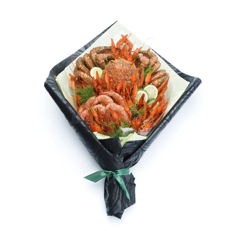 Luxueuze gift aan vrienden in de vorm van een boeket van gekookte garnalen, rivierkreeften, krab op een witte achtergrond stock foto