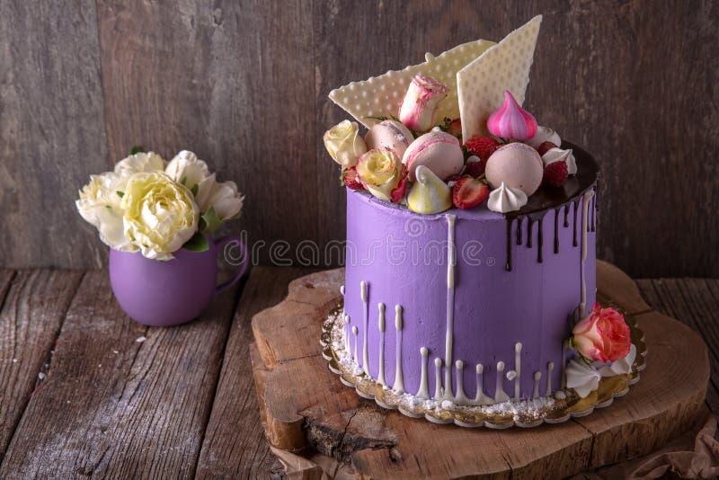 Luxueuze Purpere die cake met een bise, een heemst, bessen en verse bloemen wordt verfraaid royalty-vrije stock foto's