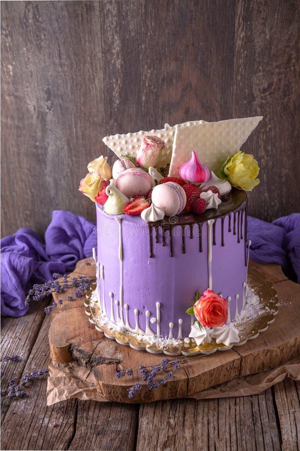 Luxueuze Purpere die cake met een bise, een heemst, bessen en verse bloemen wordt verfraaid stock foto's