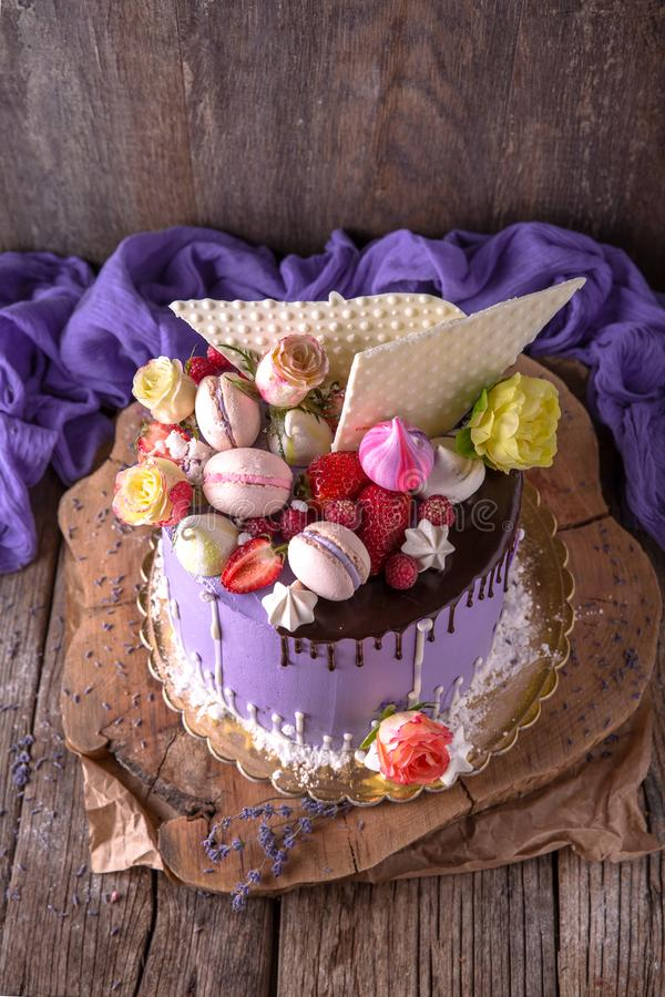 Luxueuze Purpere die cake met een bise, een heemst, bessen en verse bloemen wordt verfraaid royalty-vrije stock afbeelding