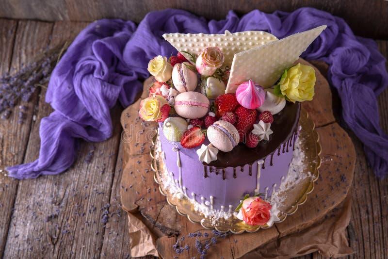 Luxueuze Purpere die cake met een bise, een heemst, bessen en verse bloemen wordt verfraaid royalty-vrije stock afbeeldingen