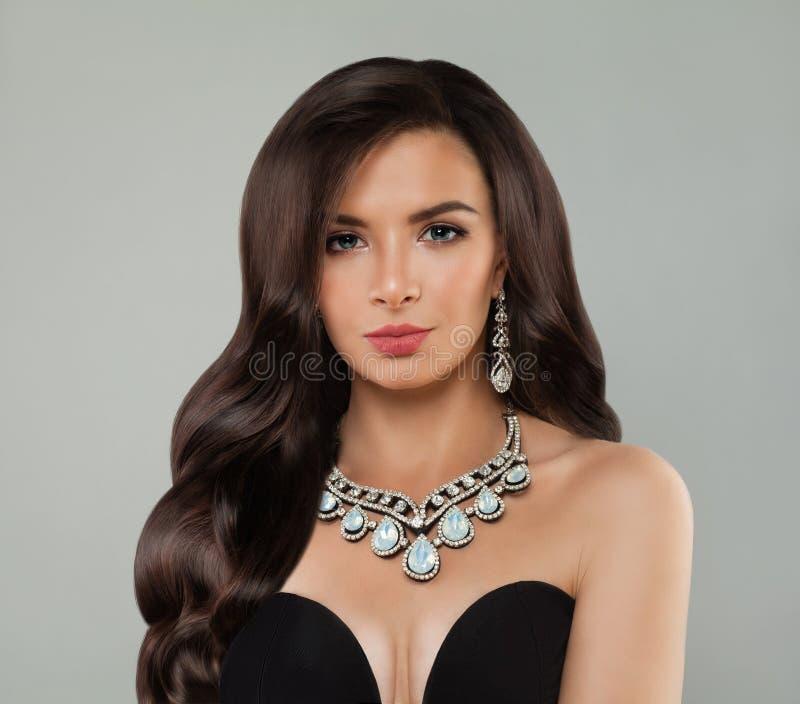 Luxueuze vrouw met make-up, lange krullende haar en diamanthalsband, manierportret stock foto