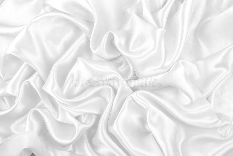 Luxuriös vom glatten weißen Seiden- oder Satingewebebeschaffenheitshintergrund stockfoto