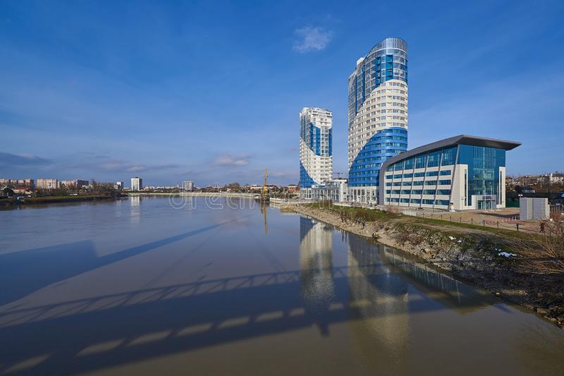Luxuriöse blau-weiße Wolkenkratzer und ein gelber Kran auf einem Lastkahn werden im Kuban-Fluss reflektiert stockfoto