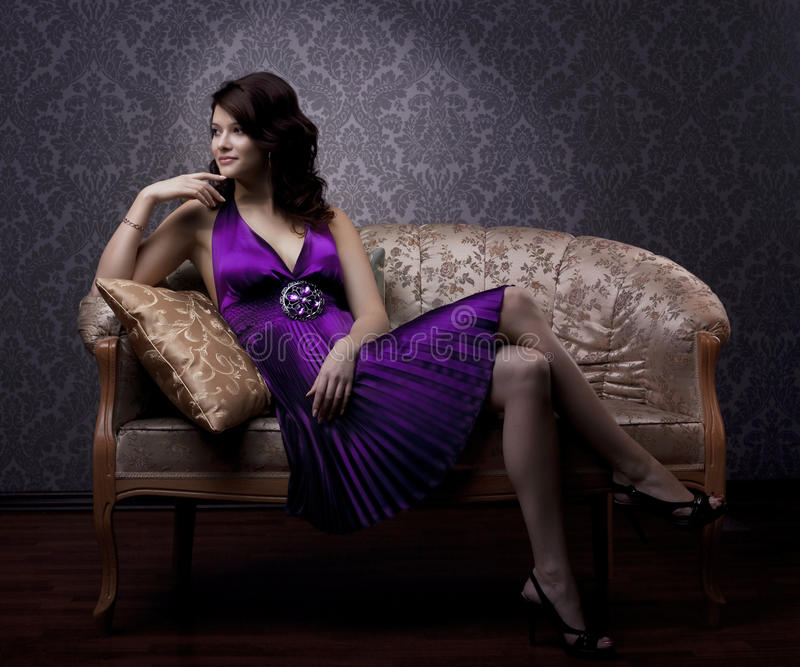Luxuriöse Frau, die auf einer Goldweinlesecouch sitzt lizenzfreie stockfotografie