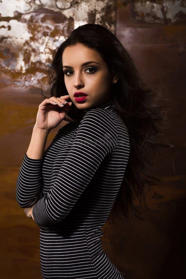 Luxuriöse gebräunte junge Frau mit dem hellen Make-up, das am Studio aufwirft lizenzfreie stockfotografie
