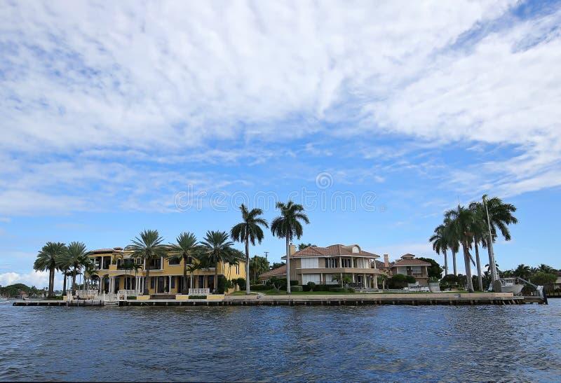 Luxuriöse Ufergegendhäuser umgeben durch Wasser- und Palmen stockfoto