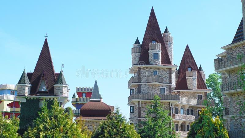 Luxuri?ses Hotel im viktorianischen Stil, untergetaucht in den sch?nen B?umen und in den B?schen D?cher mit spiers auf einem Hint lizenzfreie stockfotos