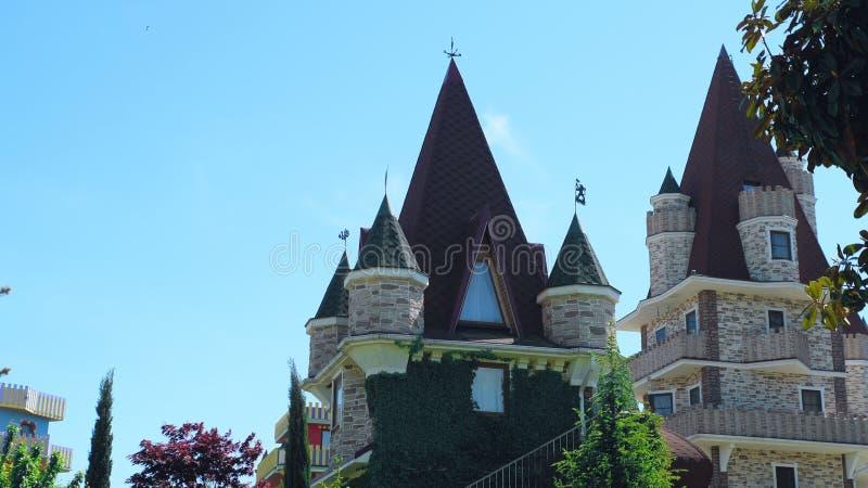 Luxuri?ses Hotel im viktorianischen Stil, untergetaucht in den sch?nen B?umen und in den B?schen D?cher mit spiers auf einem Hint stockbild