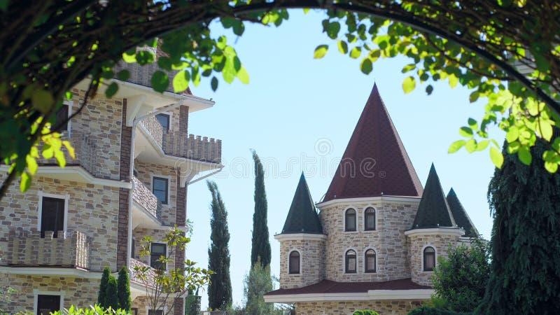 Luxuri?ses Hotel im viktorianischen Stil, untergetaucht in den sch?nen B?umen und in den B?schen D?cher mit spiers auf einem Hint stockfotos