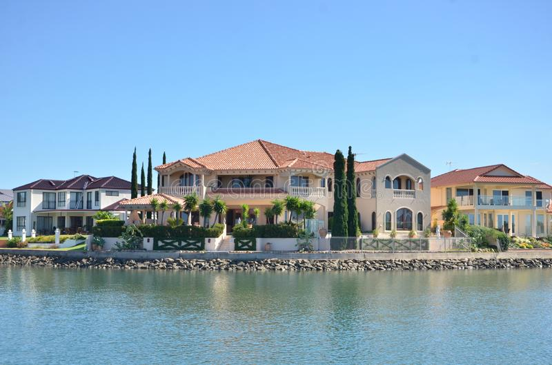 Luxuries houses along  the river in Australia. With green trees and riverbank stock images