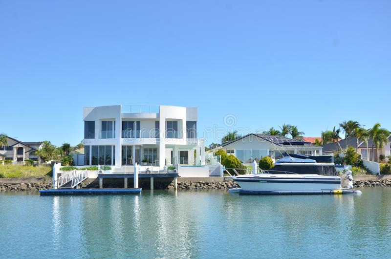 Luxuries houses along  the river in Australia. With green trees and riverbank royalty free stock image