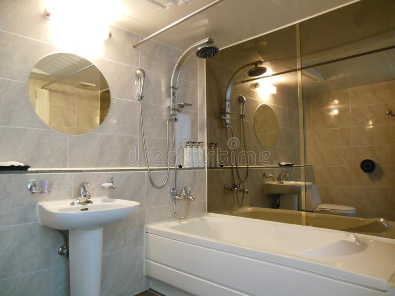 Luxurious bathroom mirrors, bathtub, basin nobody. Luxurious bathroom with tiles, mirrors, shower, white bathtub, washbasin nobody present stock image