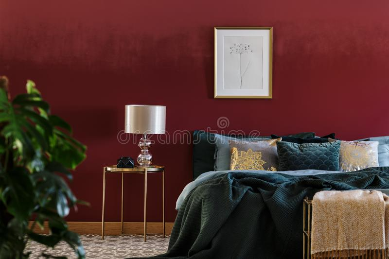 Luxurious bedroom interior with poster. Lamp on a gold table next to green bed in luxurious bedroom interior with poster on red wall stock photography