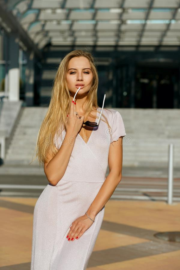 Luxurious blonde woman wearing trendy dress and sunglasses posing at the street in soft evening light stock image