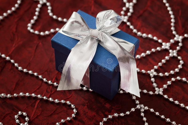 Luxurious blue gift box with a silver ribbon on a red shiny cloth and decorative silver string of pearls. royalty free stock images