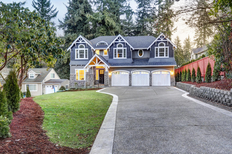 Luxurious blue home with three attached garage spaces. Luxurious home exterior with blue vinyl siding and white trim. Long concrete driveway lead to three stock photography