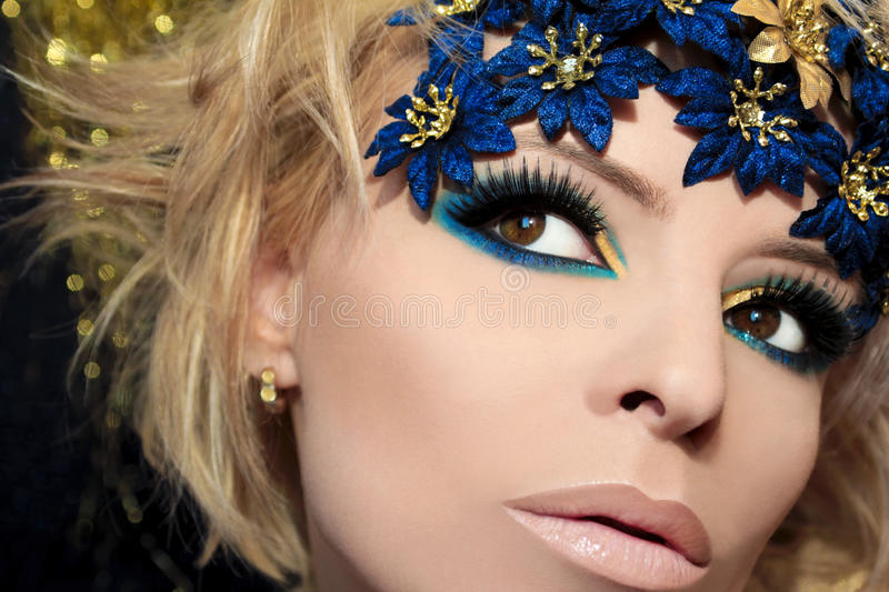 Luxurious blue makeup. Luxurious blue makeup on a girl with blond hair and decorative flowers on her head stock photos
