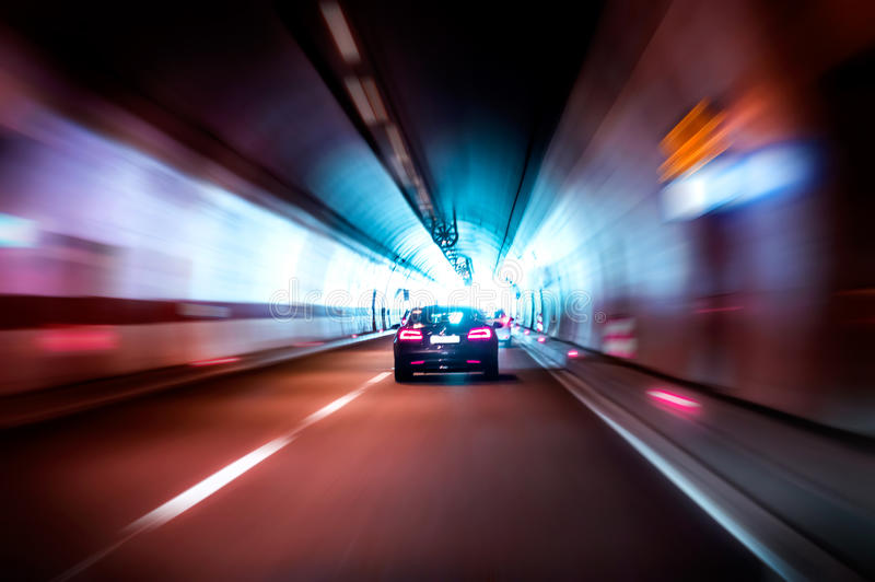 Luxurious car rides fast in a dark tunnel royalty free stock photography