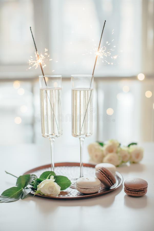 Luxurious champagne wedding party with white roses and macaron d. Esserts, holiday celebration with wine and sparklers stock photos