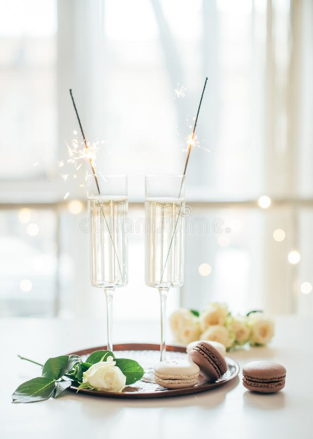 Luxurious champagne wedding party with white roses and macaron d. Esserts, holiday celebration with wine and sparklers royalty free stock photos