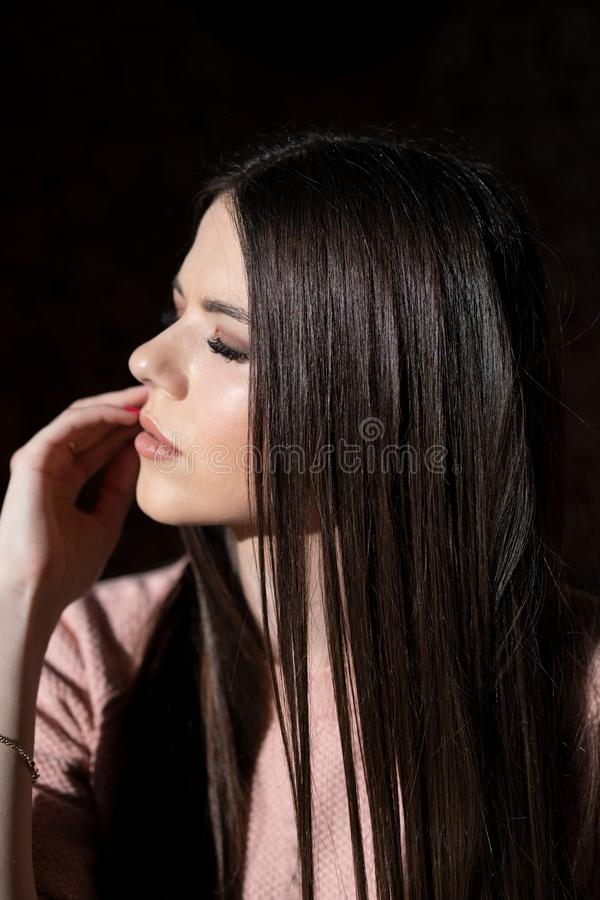 Luxurious dark hair. Beautiful young girl with closed eyes stock photo