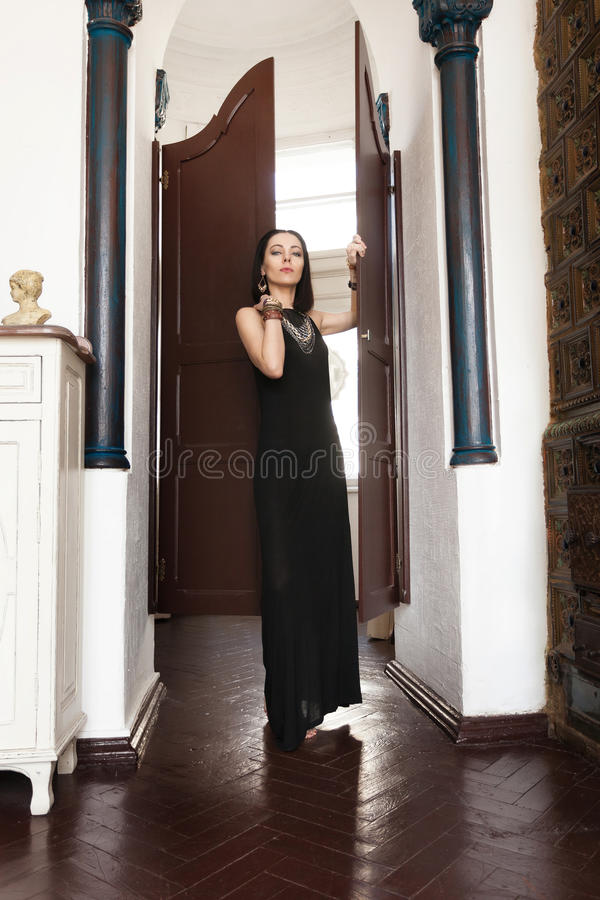 Luxurious dark-haired woman in a black dress and a massive gold jewelry stands in the doorway. Mistress of the estate invite her guests. Oriental palace, white royalty free stock photography