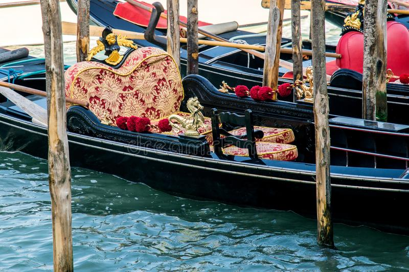 The luxurious decoration of the Venetian gondola, which is moored at the pier. royalty free stock image