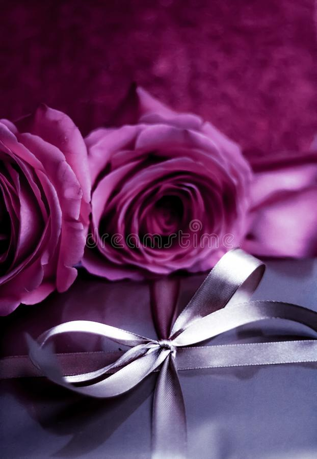 Luxury holiday silver gift box and pink roses as Christmas, Valentines Day or birthday present. Luxurious design, shop sale promotion and happy surprise concept stock photo