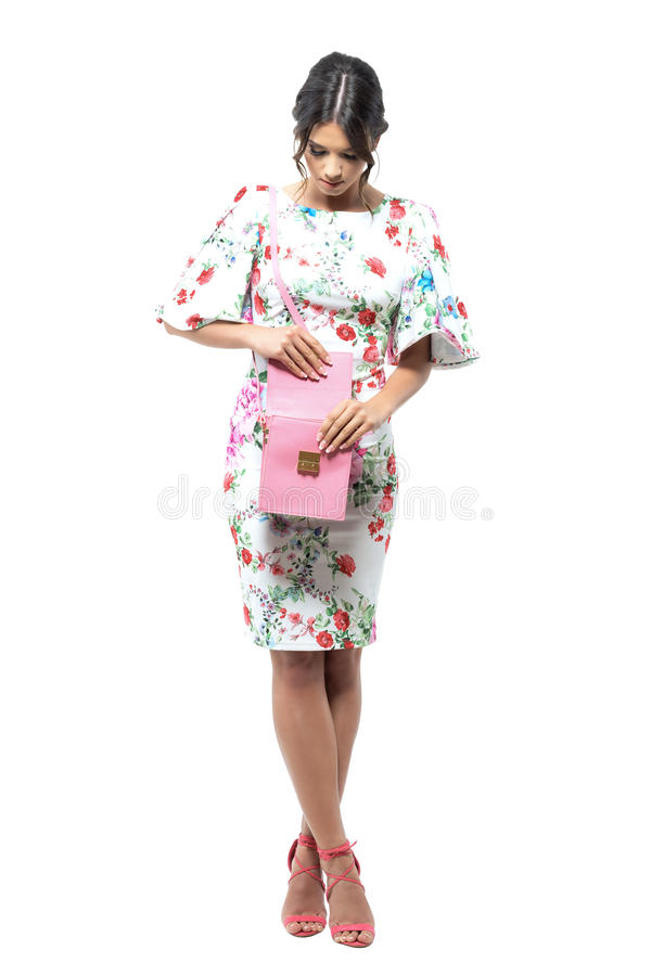 Luxurious elegant woman looking in pink handbag searching for something. Full body length portrait isolated on white background stock photography