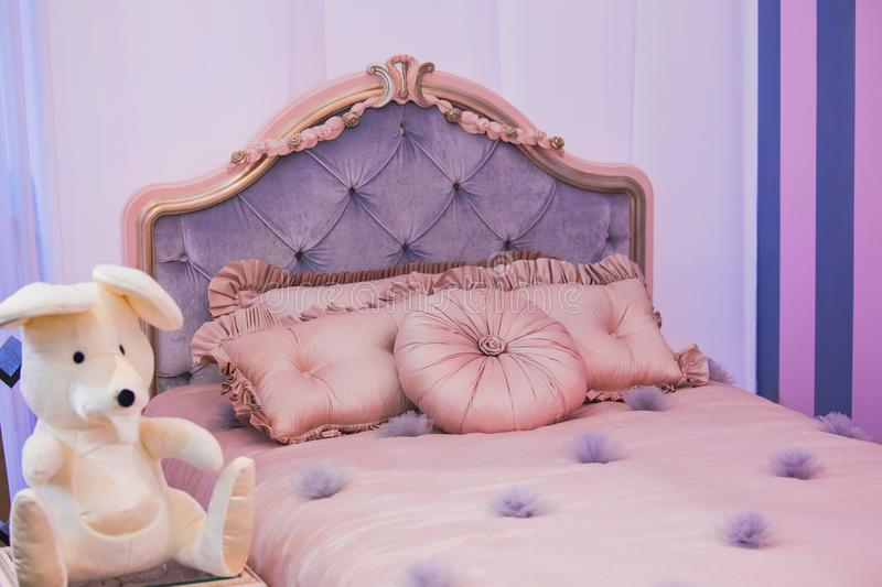 Luxurious expensive interior design of the children`s girl room in the old style. Purple bed, silk pillows royalty free stock photography