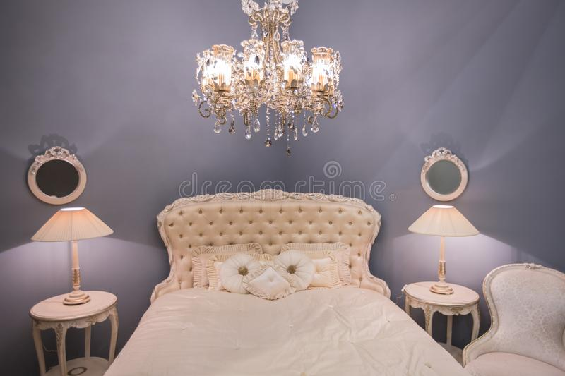 Luxurious expensive interior design of the children`s girl room in the old style. White bed, silk pillows, bedside tables with ta stock photos