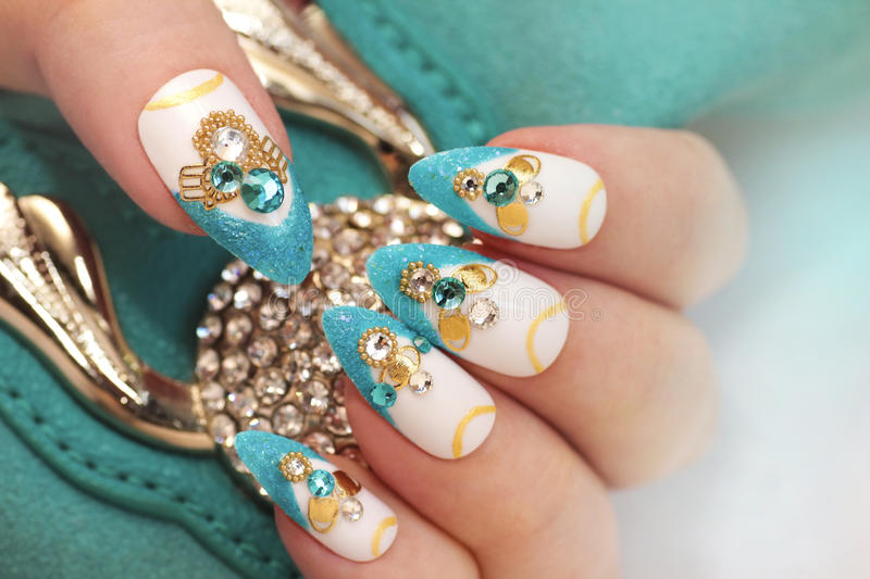 Luxurious glamorous sandy blue French manicure. Luxurious glamorous sandy blue French manicure with rhinestones,boulongne and gold plated women`s nails closeup stock photos