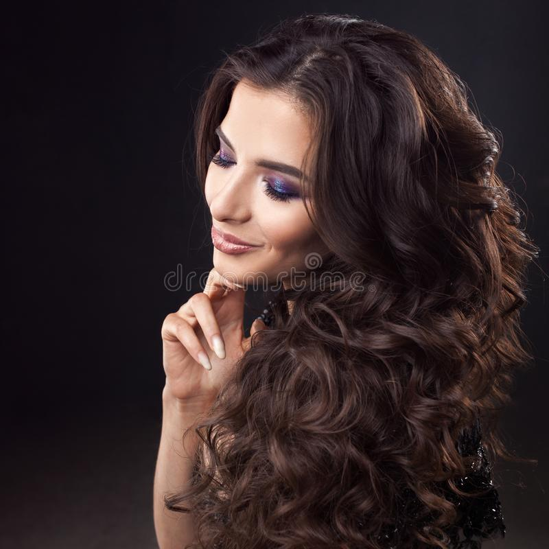 Luxurious hair. Portrait of a young attractive woman with gorgeous curly hair. Attractive brunette royalty free stock images