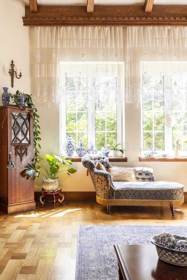 Luxurious living room interior with blue chaise lounge next to t. He window and expensive china on a wooden cupboard. Real photo stock photo