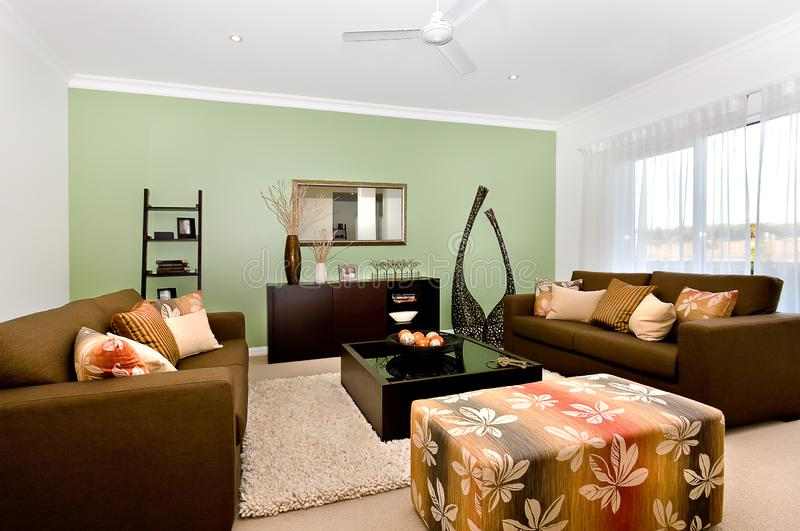Luxurious living room of a modern house interior with big and fancy sofas and many ornamental items stock image