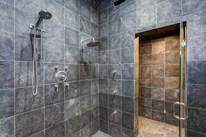 Luxurious mansion walk-in shower with black square tiled walls. Luxurious mansion wet room style shower with black square tiled walls framing wall mount rainfall royalty free stock photography