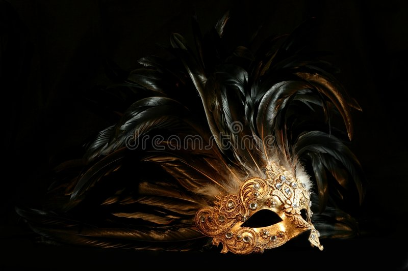 Luxurious mask. A luxurious golden mask with long feathers on a black background royalty free stock photography