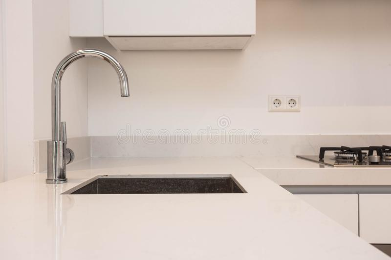 Luxurious modern kitchen with sink, Contemporary kitchen unit with chromed water tap modern white clean concept stock photography