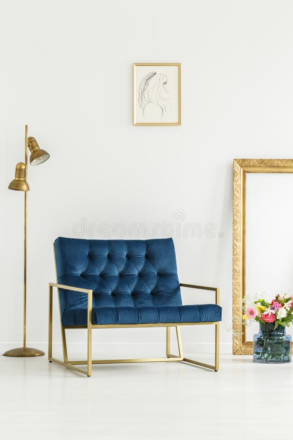 A luxurious, navy blue armchair. Golden elements,framed art and a colorful flowers bouquet in a white living room interior stock photography