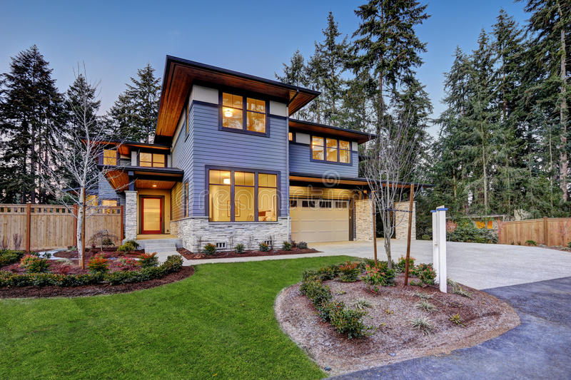 Luxurious new construction home in Bellevue, WA. Modern style home boasts two car garage framed by blue siding and natural stone wall trim. Northwest, USA royalty free stock photos