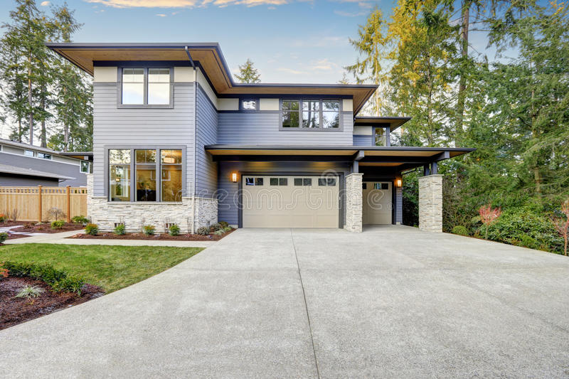 Luxurious new construction home in Bellevue, WA. Modern style home boasts two car garage framed by blue siding and natural stone wall trim. Northwest, USA stock photo