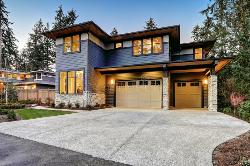 Luxurious new construction home in Bellevue, WA. Modern style home boasts two car garage framed by blue siding and natural stone wall trim. Northwest, USA stock photography