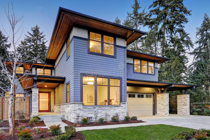 Luxurious new construction home in Bellevue, WA. Modern style home boasts two car garage framed by blue siding and natural stone wall trim. Northwest, USA royalty free stock image