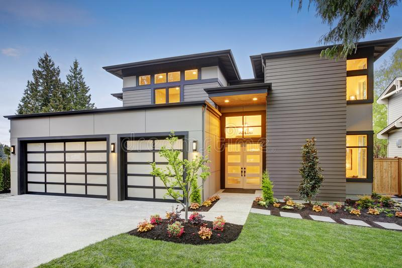 Luxurious new construction home in Bellevue, WA. Modern style home boasts two car garage spaces with glass folding doors illuminated by scones. Northwest, USA stock photos