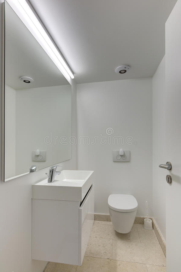 Luxurious bathroom. An image of a modern upscale bathroom interior in a new luxurious office building. Fitted with large mirror on the wall and white sink area stock image